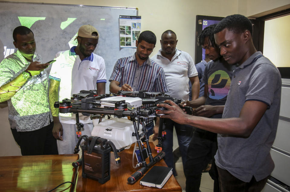 In this photo taken Thursday, Oct. 31, 2019, trainee drone pilots from the State University of Zanzibar examine a drone to be used to spray the breeding grounds of malaria-carrying mosquitoes, at Cheju paddy farms in the southern Cheju region of the island of Zanzibar, Tanzania. Drones spraying a silicone-based liquid that spreads across the large expanses of stagnant water where malaria-carrying mosquitoes lay their eggs, are being tested to help fight the disease on the island of Zanzibar, off the coast of Tanzania. (AP Photo/Haroub Hussein)