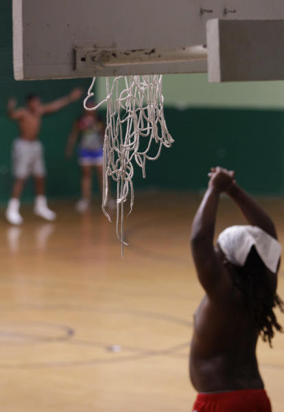 In this Thursday, July 5, 2012 photo, a student training for the school's football program works out beneath a ripped basketball net inside one of the gymnasiums at the 88-year-old Charles E. Gorton High School in Yonkers, N.Y. The school district is looking for investors to pay for a $1.7 billion overhaul of dozens of schools like this one, which is 43% over-enrolled and needs millions of dollars of renovations. (AP Photo/Kathy Willens)