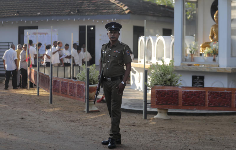 Sri Lankans queue up to cast their votes as a police officer stands guard at a polling station during the presidential election in Colombo, Sri Lanka, Saturday, Nov. 16, 2019. Polls opened in Sri Lanka's presidential election Saturday after weeks of campaigning that largely focused on national security and religious extremism in the backdrop of the deadly Islamic State-inspired suicide bomb attacks on Easter Sunday. (AP Photo/Eranga Jayawardena)