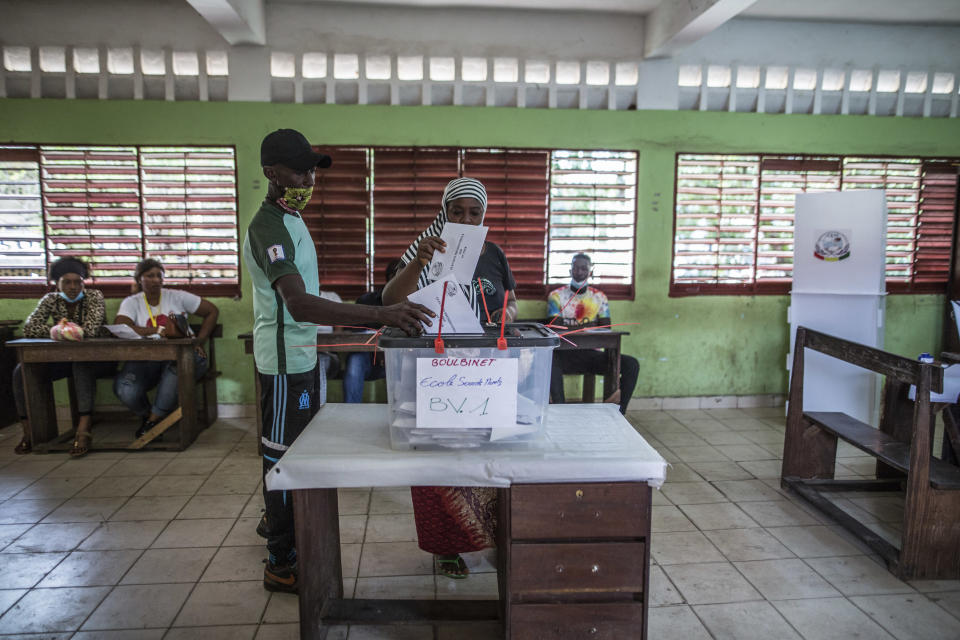 A woman votes at a school in Conakry, Guinea, Sunday Oct. 18, 2020. Guineans head to the polls to elect their president, choosing between incumbent Alpha Conde who is seeking a third term and historical opponent Cellou Dalein Diallo. (AP Photo/Sadak Souici)