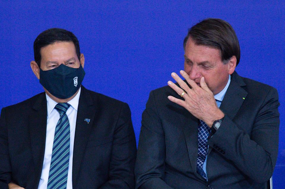 BRASILIA, BRAZIL -NOVEMBER09: BrazilianVice President Hamilton Mourão and President of Brazil Jair Bolsonaro react during Volunteering Alliance launch amidst the coronavirus(COVID-19) pandemic at the Planalto Palace on November09, 2020 in Brasilia.Brazil has over 5.064,000 confirmed positive cases of Coronavirus and has over 162,397 deaths. (Photo by Andressa Anholete/Getty Images)