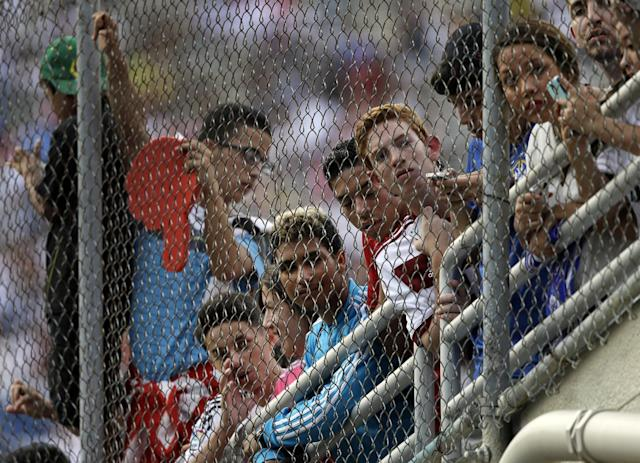 Fans line the gates along the tunnel entrance to the field at the Cotton Bowl stadium as they wait for Real Madrid and Roma players to make their way onto the field for a Guinness International Champions Cup soccer tournament match, Tuesday, July 29, 2014, in Dallas. (AP Photo/Tony Gutierrez)