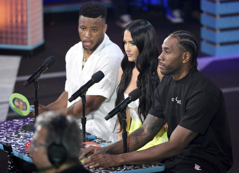 NFL player, Saquon Barkley, of the New York Giants, from left, Nikki Bella, and Kawhi Leonard judge the Pillow Fight Fight Night challenge at the Kids' Choice Sports Awards on Thursday, July 11, 2019, at the Barker Hangar in Santa Monica, Calif. (Photo by Chris Pizzello/Invision/AP)