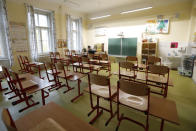 A teacher sits in an empty classroom and prepares materials for children at a closed school in Prague, Czech Republic, Wednesday, Oct. 14, 2020. Amid widespread efforts to curb the new wave of coronavirus infections in one of the hardest hit European countries, the Czech Republic closed again all its schools on Wednesday. (AP Photo/Petr David Josek)