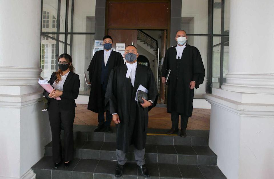 Lawyer Ong Yu Shin (centre) and his team are pictured at the Ipoh High Court September 10, 2021. — Picture by Farhan Najib