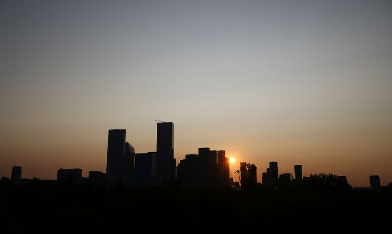 The sun rises behind Canary Wharf financial district in London