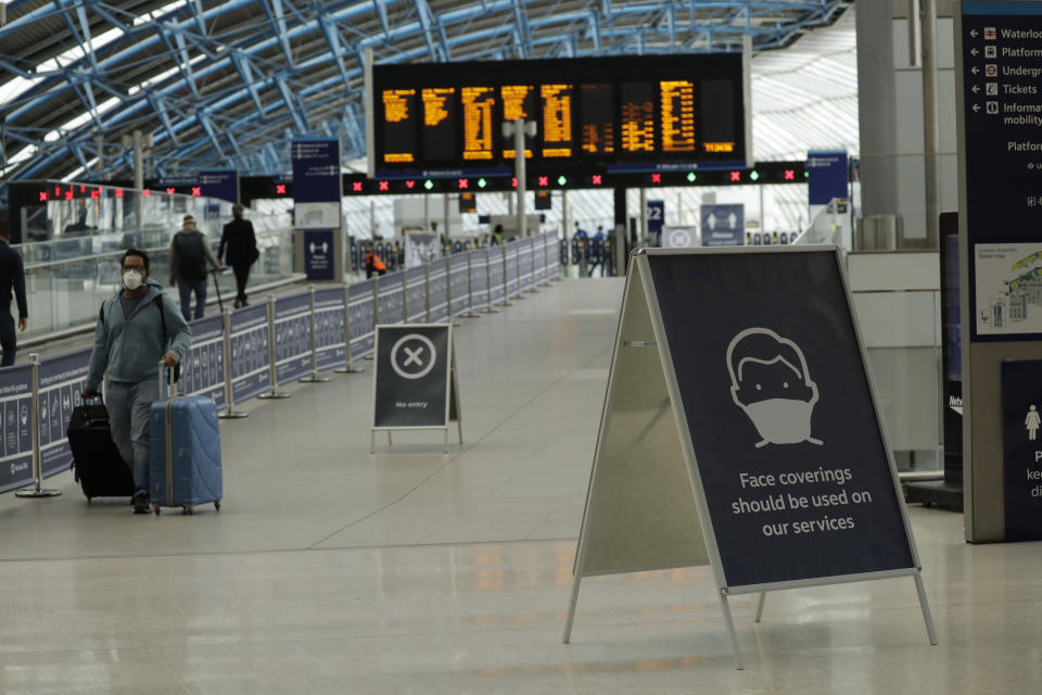 A sign recommending people wear face coverings to help stop the spread of coronavirus is displayed in Waterloo station, London, Thursday, June 4, 2020. Waterloo station, which is wide recognised as the busiest train station in Britain, is still much quieter than normal as most commuters are working from home and not commuting into central London offices. (AP Photo/Matt Dunham)