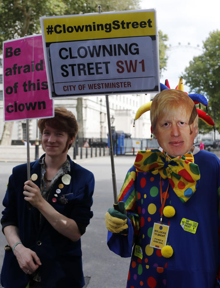 A protestor with a mask of Britain's Prime Minister Boris Johnson demonstrates outside Downing Street in London, Wednesday, Aug. 28, 2019. Prime Minister Johnson has written to fellow lawmakers explaining his decision to ask Queen Elizabeth II to suspend Parliament as part of the government plans before the Brexit split from Europe. (AP Photo/Frank Augstein)