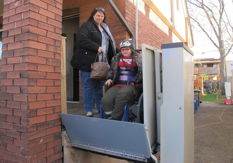 """In this Nov. 21, 2017 photo, Jodi Dean helps her wheelchair-bound daughter Madison, who suffers epilepsy and severe osteoporosis, on an elevator as they leave home for a doctor's visit in Hamilton, Ont. The mother of three received her first basic income check last month and said the extra money gave her family """"the breathing room to not have to stress to put food on the table."""" (Photo: AP Photo/Rob Gillies via CP)"""