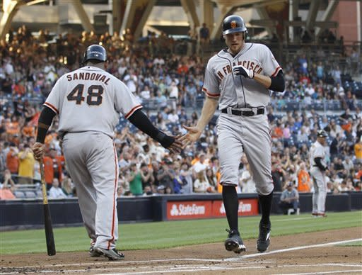 San Francisco Giants' Hunter Pence gets a low-five from Pablo Sandoval as he crosses home plate with a three-run home run during the first inning of a baseball game against the San Diego Padres on Saturday, Sept. 29, 2012, in San Diego. (AP Photo/Lenny Ignelzi)