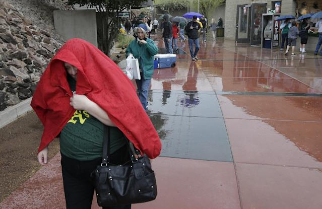 Fans cover themselves as rain falls before the Oakland Athletics are scheduled to play the Texas Rangers in a spring training baseball game Saturday, March 1, 2014, in Phoenix. (AP Photo/Gregory Bull)