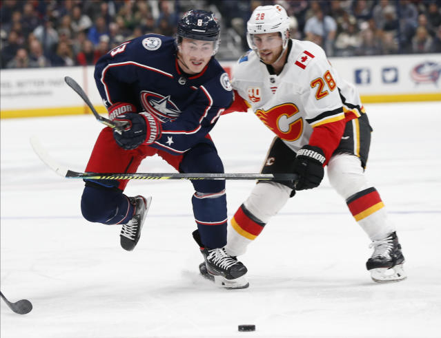 Columbus Blue Jackets' Zach Werenski, left, and Calgary Flames' Elias Lindholm, of Sweden, chase the puck during the second period of an NHL hockey game Saturday, Nov. 2, 2019, in Columbus, Ohio. (AP Photo/Jay LaPrete)