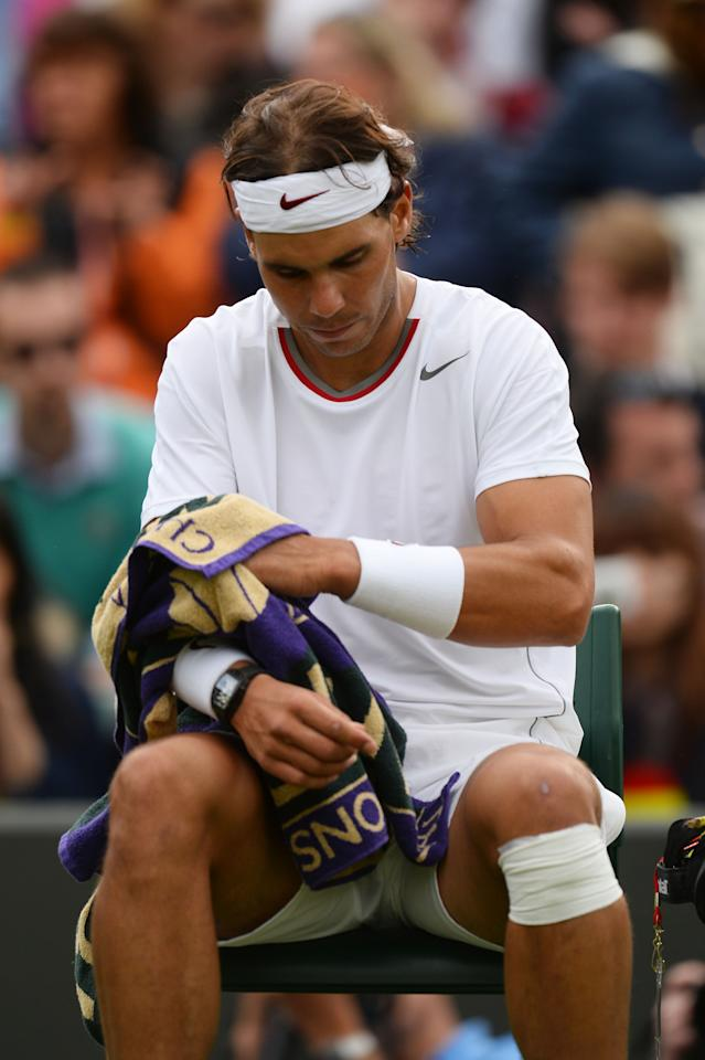 LONDON, ENGLAND - JUNE 24: A dejected Rafael Nadal of Spain looks on during his Gentlemen's Singles first round match against Steve Darcis of Belgium on day one of the Wimbledon Lawn Tennis Championships at the All England Lawn Tennis and Croquet Club on June 24, 2013 in London, England. (Photo by Mike Hewitt/Getty Images)