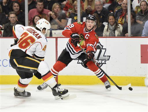 Chicago Blackhawks' Jonathan Toews, right, passes the puck as Calgary Flames' Dennis Wideman defends during the second period of an NHL hockey game, Friday, April 26, 2013 in Chicago. (AP Photo/Brian Kersey)