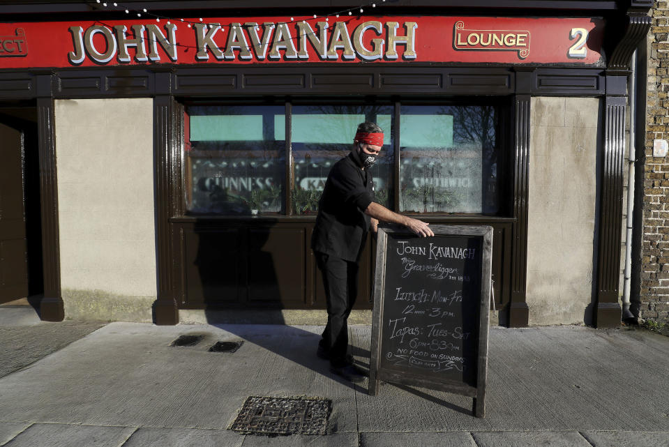 Ciaran Kavanagh, one of the seventh generation of John Kavanagh's bar, makes preparations as they are preparing to reopen the lounge seven days a week. Thousands of restaurants, cafes and gastropubs are reopening their doors today as pandemic restrictions are eased ahead of Christmas. (Brian Lawless/PA via AP)