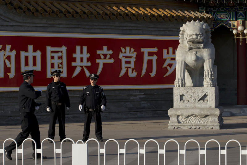 "Chinese policemen guard the entrance to the Zhongnanhai leadership compound near the Chinese characters for ""Long live the Chinese Communist Party"" in Beijing Tuesday, Nov. 12, 2013. In a brief statement issued after a four-day Communist Party conference aimed at producing a reform blueprint for the next decade China's leaders have promised to give the free market an even bigger role as they overhaul the worn-out growth model of their slowing, government-dominated economy. (AP Photo/Ng Han Guan)"