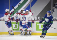 Montreal Canadiens' Ben Chiarot, Phillip Danault, Tomas Tatar and Brendan Gallagher, from left, celebrate Gallagher's goal as Vancouver Canucks' Quinn Hughes skates past them during the third period of an NHL hockey game Saturday, Jan. 23, 2021, Vancouver, British Columbia. (Darryl Dyck/The Canadian Press via AP)