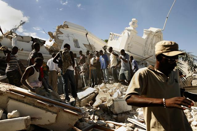 <p>The Department of Justice was flattened by the earthquake. Men gather to try to get to those still buried in the rubble without any assistance in Port-au-Prince, Haiti, Jan.13, 2010. (Photo: Carolyn Cole/Los Angeles Times via Getty Images) </p>