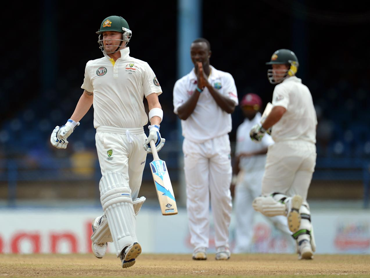 Australian batsmen Michael Clarke (L) and Ricky Ponting (R) run as West Indies bowler Kemar Roach (C) reacts during the fourth day of the second-of-three Test matches between Australia and West Indies April 18, 2012 at Queen's Park Oval in Port of Spain, Trinidad.