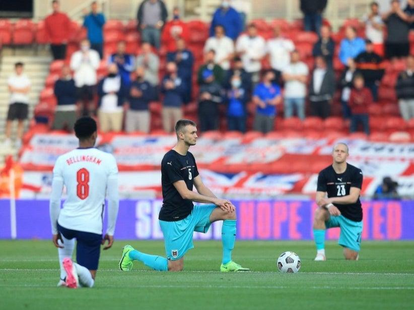 <p>England and Austria players take the knee</p> (POOL/AFP via Getty Images)