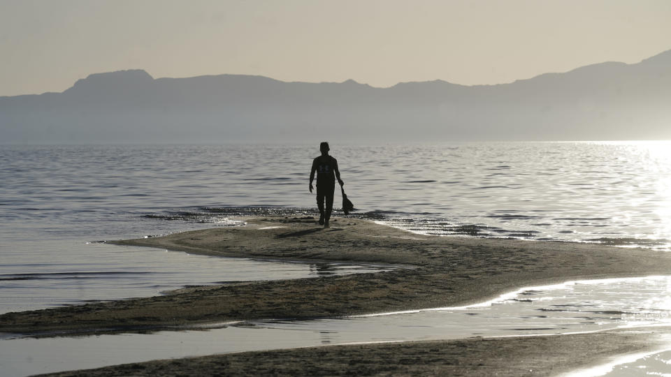 FILE - A man walks along a sand bar at the receding edge of the Great Salt Lake on June 13, 2021, near Salt Lake City. The water levels at the Great Salt Lake have hit a historic low, a grim milestone for the largest natural lake west of the Mississippi River that comes as a megadrought grips the region. (AP Photo/Rick Bowmer, File)