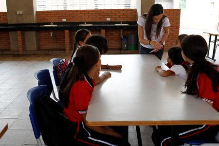 "Ana Isabel Otero, Director of the NGO ""Comparte por una vida"" (Share for a life), talks with children as they have a snack, part of the NGO health program, at La Frontera school in Cucuta, Colombia February 5, 2019. Picture taken February 5, 2019. REUTERS/Marco Bello"