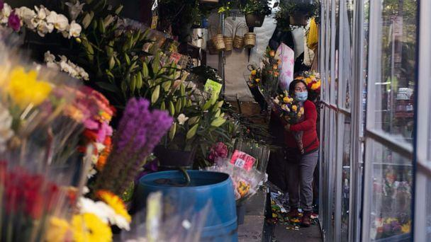PHOTO: A woman holds flowers inside a bodega on May 10, 2020 in New York City. (Jeenah Moon/Getty Images)