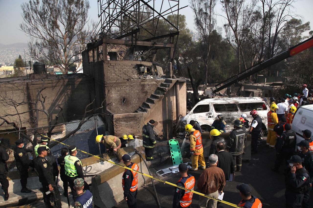 Firefighters work next to destroyed houses and vehicles after a gas tanker truck exploded on a nearby highway in the Mexico City suburb of Ecatepec early Tuesday, May 7, 2013. The blast killed and injured dozens, according to the Citizen Safety Department of Mexico State. Officials did not rule out the possibility the death toll could rise as emergency workers continued sifting through the charred remains of vehicles and homes built near the highway on the northern edge of the metropolis. (AP Photo/Marco Ugarte)