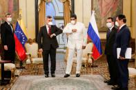 FILE PHOTO: Venezuela's President Nicolas Maduro and Russia's ambassador in Venezuela Sergey Melik-Bagdasarov, touch their elbows while wearing masks due to coronavirus disease while (COVID-19) outbreak at Miraflores Palace in Caracas
