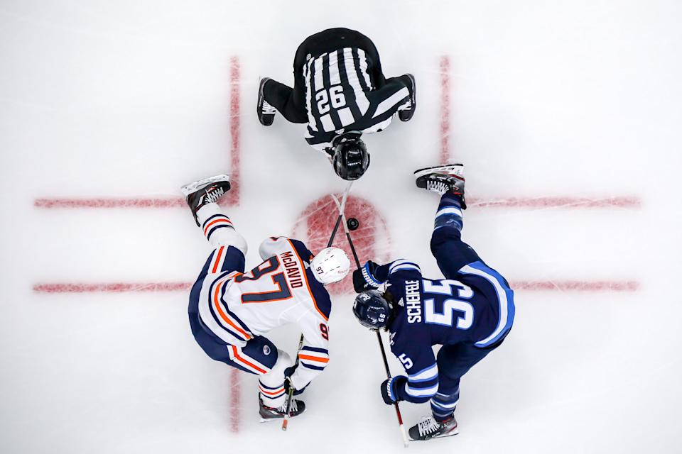 WINNIPEG, MB - APRIL 28: Connor McDavid #97 of the Edmonton Oilers and Mark Scheifele #55 of the Winnipeg Jets take a first period face-off at the Bell MTS Place on April 28, 2021 in Winnipeg, Manitoba, Canada. (Photo by Jonathan Kozub/NHLI via Getty Images)