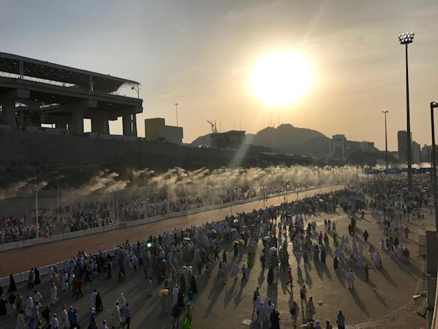 <p>Prospective pilgrims walk on the road, which has water spray cooling system, to stone Jamarat pillars that symbolize the devil as a part of the annual Islamic hajj pilgrimage during the first day of Eid Al-Adha (Feast of Sacrifice) in Mecca, Saudi Arabia on Sept.3, 2017. (Photo: Firat Yurdakul/Anadolu Agency/Getty Images) </p>