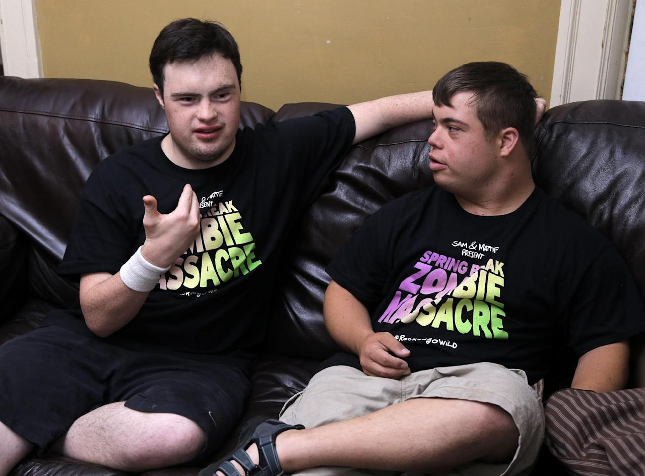"In this July 12, 2016 photo, Sam Suchmann, left, and Mattie Zufelt speak during an interview with an AP reporter at Sam's home in Providence, R.I. Suchmann and Zufelt, best friends with Down syndrome, are living their dreams of making a full-length, epic zombie movie and becoming celebrities. The duo premiered their movie, ""Spring Break Zombie Massacre,"" in Providence last week, have been invited to several film festivals in North America, and are scheduled to appear on ""Conan"" Thursday. (AP Photo/Elise Amendola)"