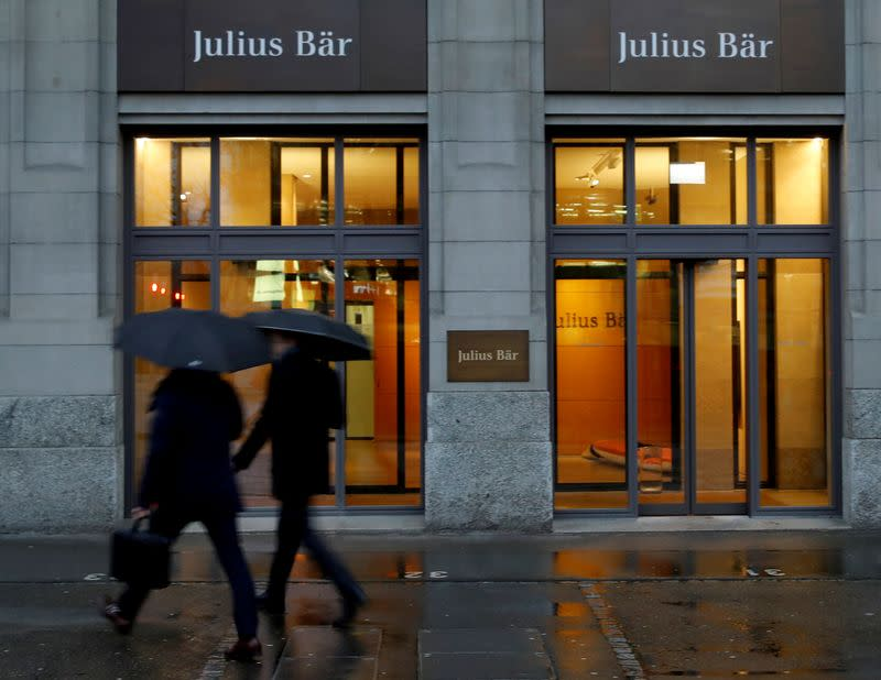 FILE PHOTO: People walk past a branch of Swiss bank Julius Baer in Zurich