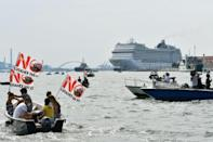 """Environmental protesters from the """"No Grandi Navi"""" group demonstrate aboard small boats"""