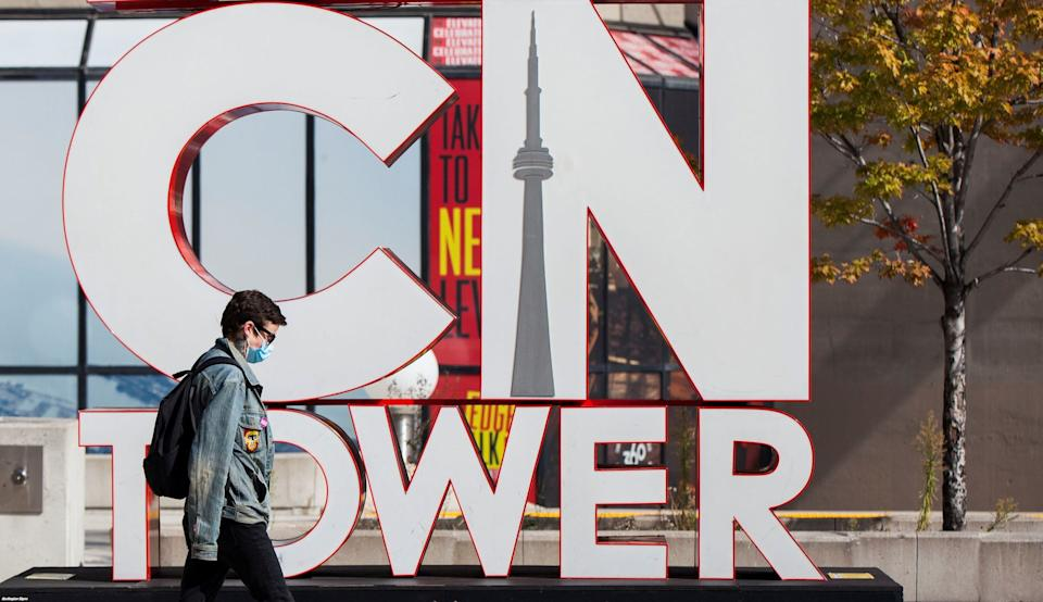A man wearing a face mask walks past the CN Tower's sign in Toronto, Oct. 3, 2020. Canada's economic recovery appears to be running out of steam amid a second wave of COVID-19, CIBC says. (Photo: Xinhua News Agency via Getty Images)