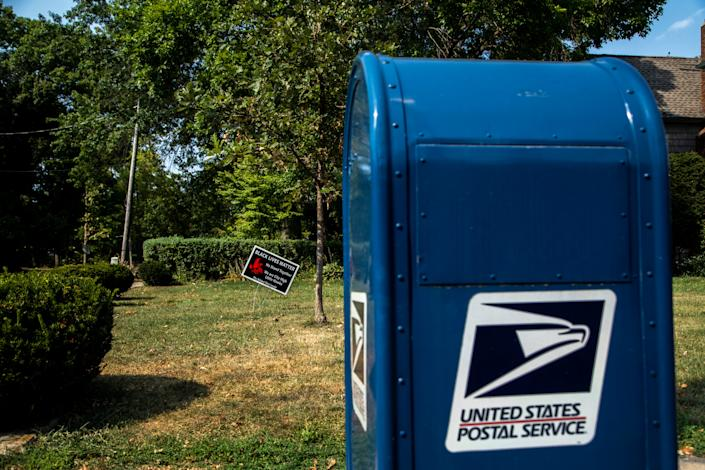 """A sign in a yard reads, """"Black Lives Matter,"""" next to a United States Postal Service (USPS) blue mail box, Tuesday, Aug. 25, 2020, on the corner of Bowery and Summit Streets in Iowa City, Iowa."""
