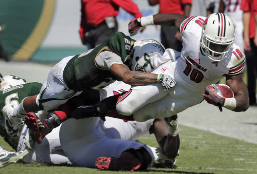 Louisville running back Dominique Brown (10) is knocked down by South Florida safety Mark Joyce (26) during the second quarter of an NCAA college football game Saturday, Oct. 26, 2013, in Tampa, Fla. (AP Photo/Chris O'Meara)
