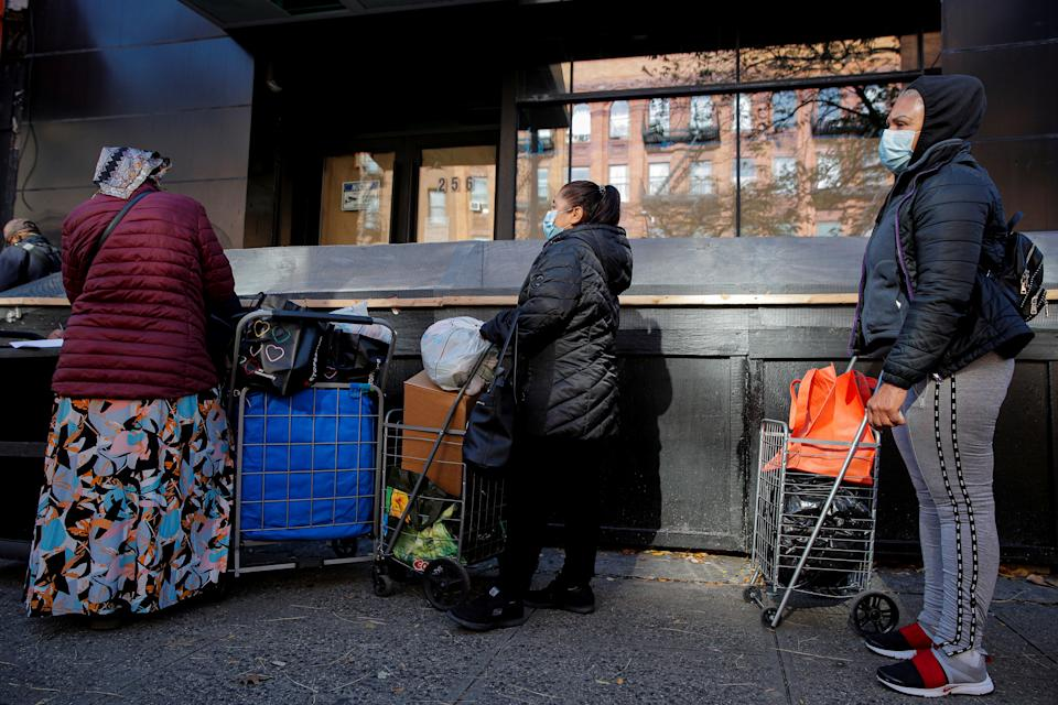 People line up to receive free holiday boxes of food from the Food Bank For New York City ahead of the Thanksgiving holiday, as the global outbreak of the coronavirus disease (COVID-19) continues, in the Harlem neighborhood of New York, U.S., November 16, 2020.  REUTERS/Brendan McDermid