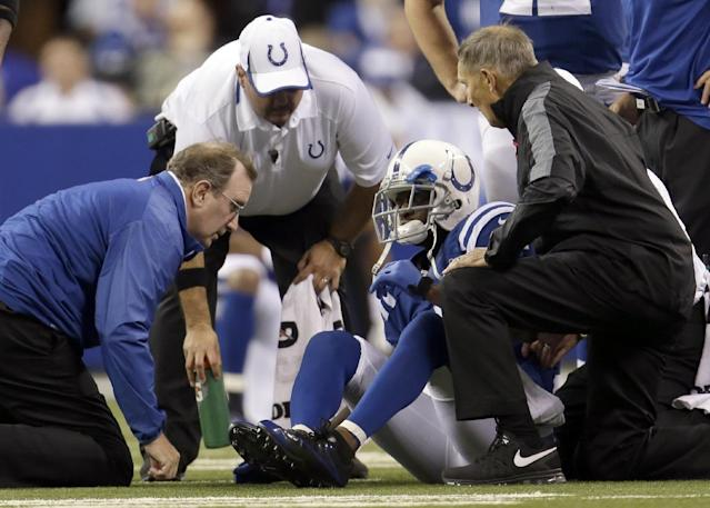 Trainers talk to Indianapolis Colts wide receiver Reggie Wayne (87) after Wayne injures his knee during the second half of an NFL football game, Sunday, Oct. 20, 2013, in Indianapolis. (AP Photo/AJ Mast)