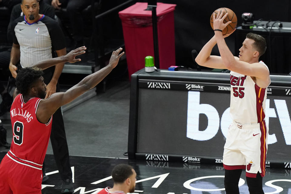 Miami Heat guard Duncan Robinson, right, shoots against Chicago Bulls forward Patrick Williams during the first half of an NBA basketball game in Chicago, Friday, March 12, 2021. (AP Photo/Nam Y. Huh)