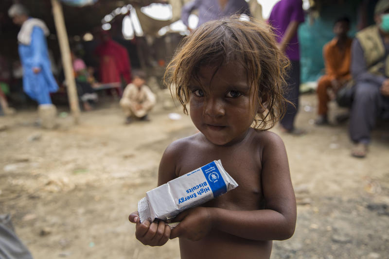 Yasmin, three, holds a packet of high-energy biscuits, part of a ration package from WFP, in Koi Goth, a slum area in KarachiSaiyna Bashir/Arete/WFP