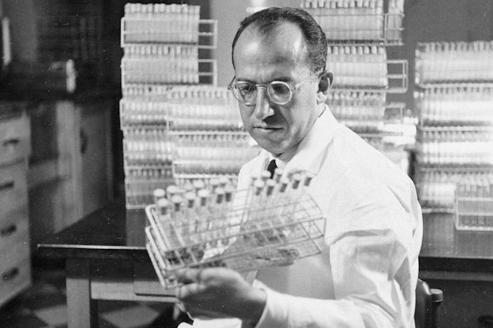 Dr.  Jonas Salk, developer of the polio vaccine, holds a rack of test tubes in his laboratory in Pittsburgh on October 7, 1954.