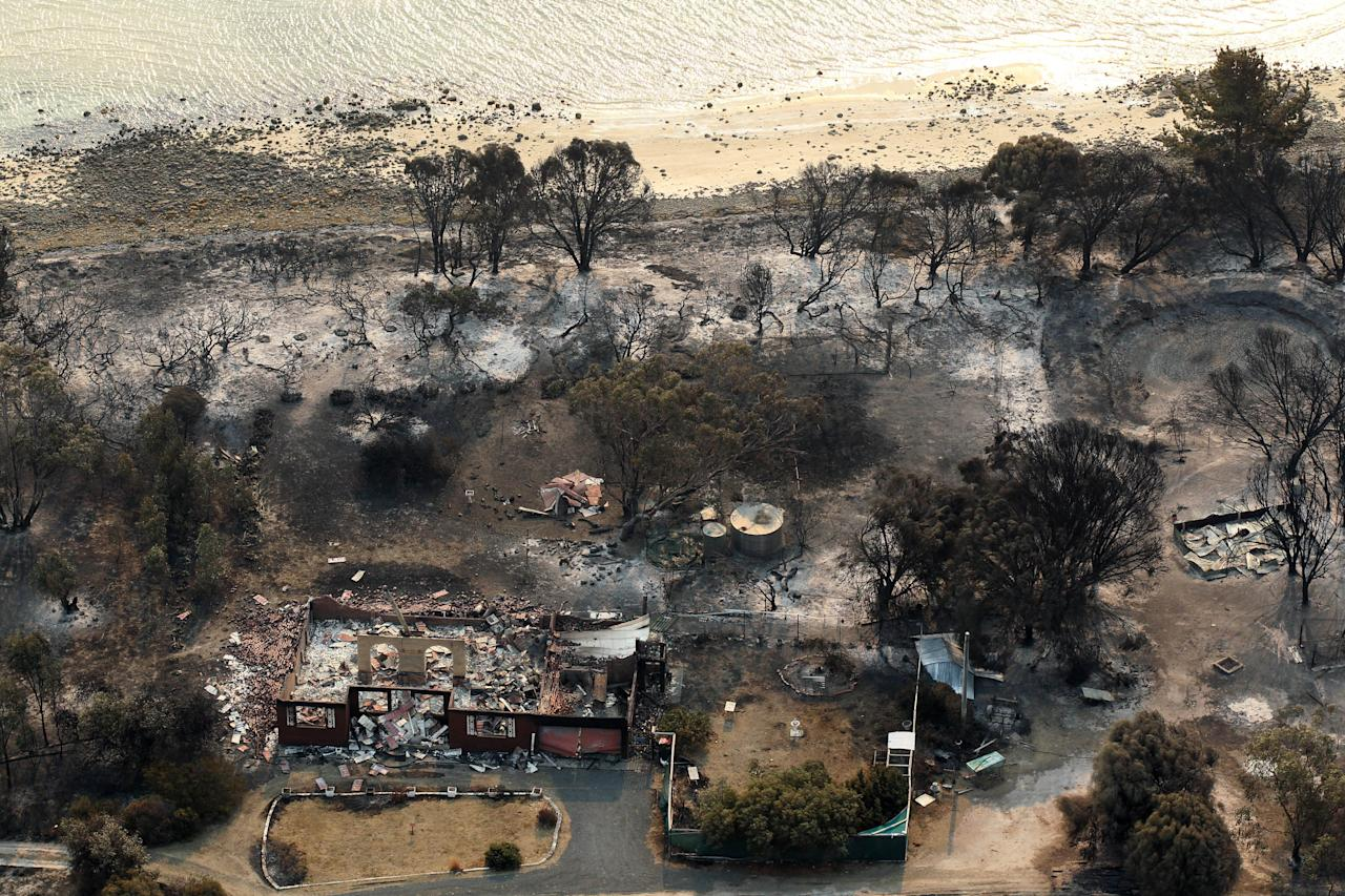 This aerial photo shows homes destroyed by a wildfire near Boomer Bay, in southern Australia, on Saturday, Jan. 5, 2013. Australian officials battled a series of wildfires amid scorching temperatures across the country on Saturday, with one blaze destroying dozens of homes in the island state of Tasmania. (AP Photo/Chris Kidd, Pool)