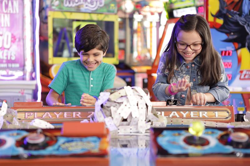 Two children playing arcade game