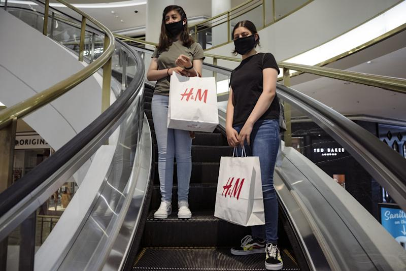 Shoppers wearing protective masks carry Hennes & Mauritz (H&M) shopping bags down an escalator at Westfield San Francisco Centre in San Francisco, California, U.S., on Thursday, June 18, 2020. San Francisco moved into Phase 2B on Monday, opening up outdoor dining and allowing customers to go inside retail stores to shop. Photographer: Michael Short/Bloomberg