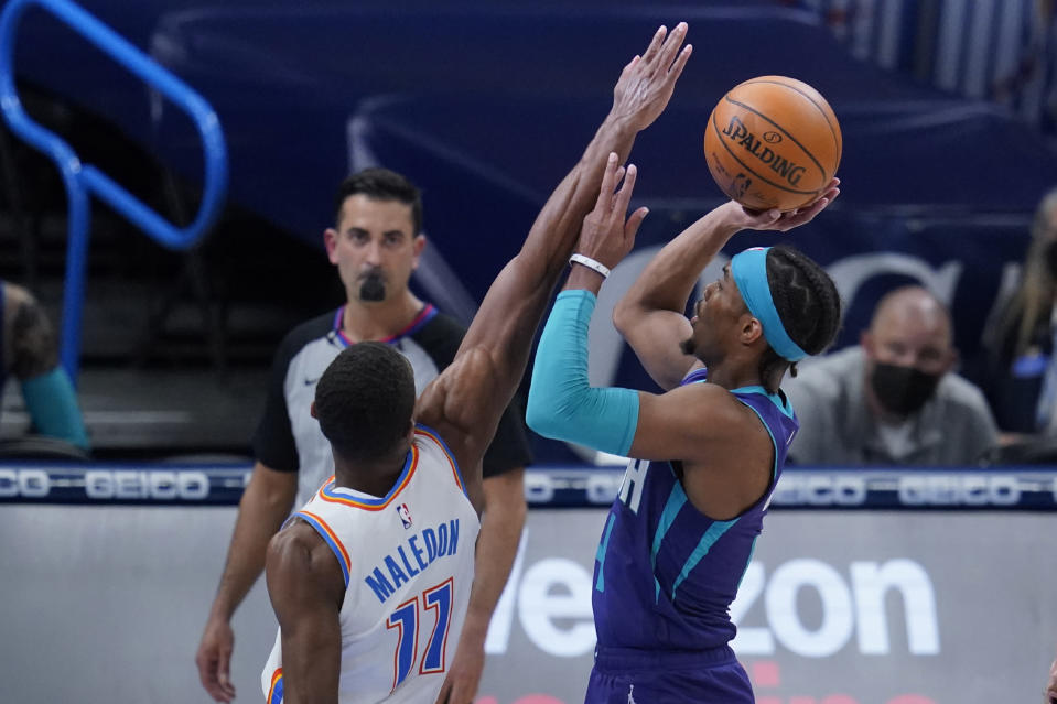 Charlotte Hornets guard Devonte' Graham, right, shoots as Oklahoma City Thunder guard Theo Maledon (11) defends in the first half of an NBA basketball game Wednesday, April 7, 2021, in Oklahoma City. (AP Photo/Sue Ogrocki)