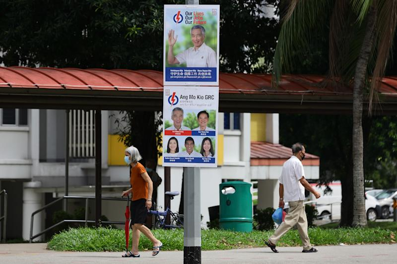 SINGAPORE - JUNE 30: People walk past a People's Action Party poster along the street on June 30, 2020 in Singapore. Singapore will go to the polls on July 10 as the ruling party, People's Action Party seeks a fresh mandate amid the coronavirus (COVID-19) pandemic. As of June 29, the total number of COVID-19 cases in the country stands at 43,361. (Photo by Suhaimi Abdullah/Getty Images)