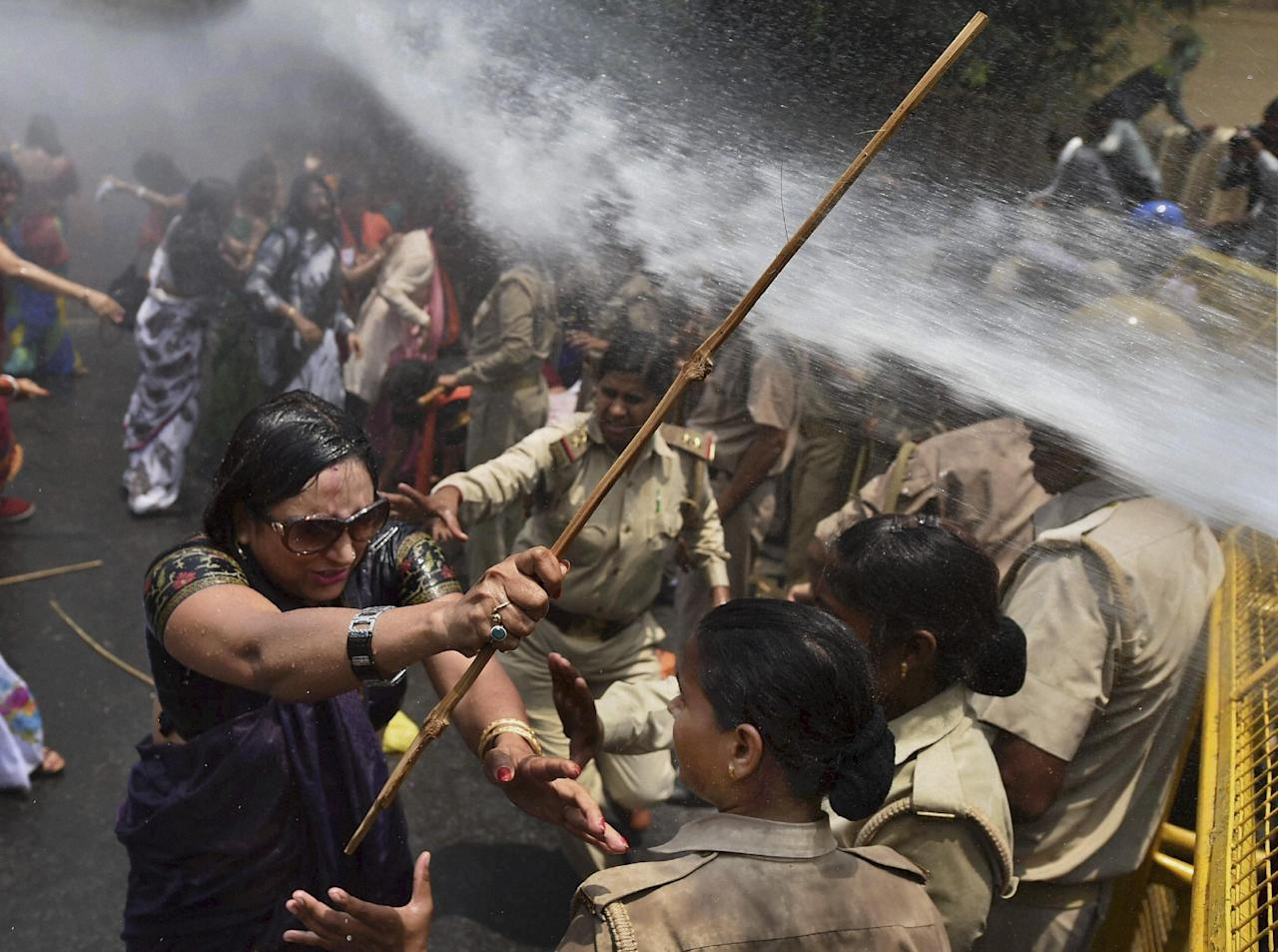 An Indian woman, left, one among the protestors demonstrating outside the office of Uttar Pradesh state chief minister Akhilesh Yadav, demanding that he crack down on an increasing number of rape and other attacks on women and girls, scuffles with police in Lucknow, India, Monday, June 2, 2014. Police used water cannons to disperse hundreds of women who were protesting Monday against a rise in violence against women in the northern Indian state where two teenagers were gang-raped last week and later found hanging from a tree. (AP Photo)