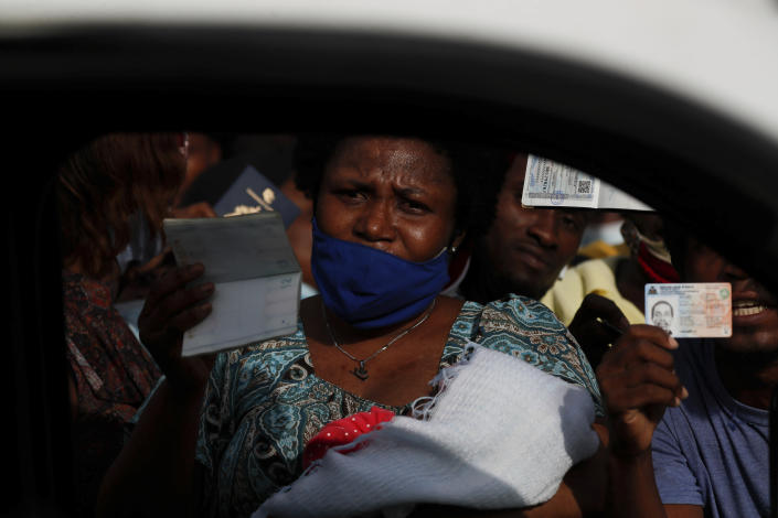"""Haitians wave their passports shouting """"Help, refugee,"""" as they gather outside the U.S. Embassy in Port-au-Prince, Haiti, Friday, July 9, 2021. A large crowd gathered outside the embassy amid rumors on radio and social media that the U.S. will be handing out exile and humanitarian visas, two days after Haitian President Jovenel Moise was assassinated in his home. (AP Photo/Joseph Odelyn)"""