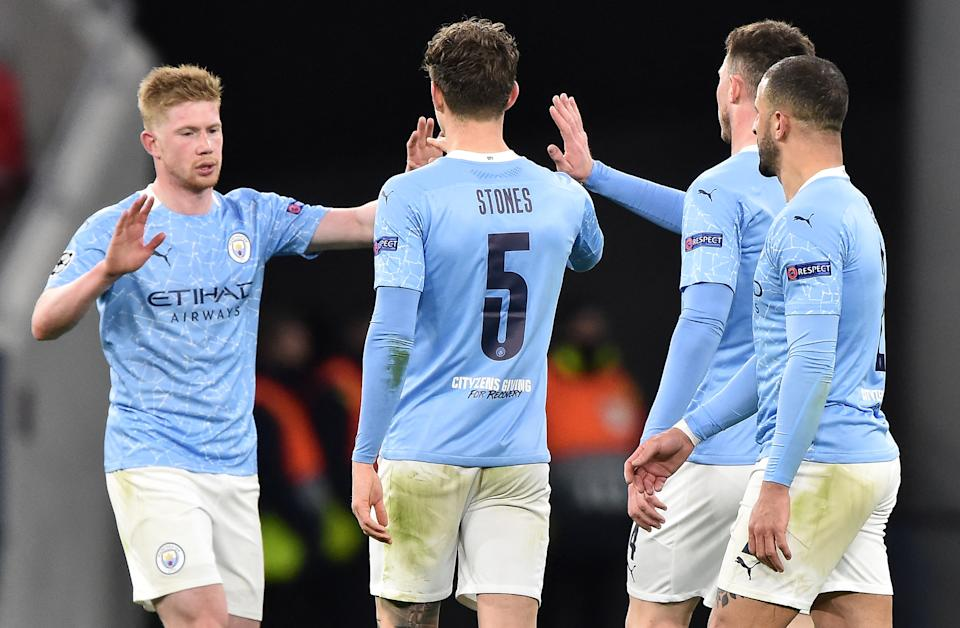 Manchester City's Belgian midfielder Kevin De Bruyne (L) celebrates with teammates at the final whistle in the UEFA Champions League, last 16, second-leg football match between Manchester City and Borussia Monchengladbach at the Puskas Arena in Budapest on March 16, 2021. - Manchester City won the match 2-0. (Photo by Attila KISBENEDEK / AFP) (Photo by ATTILA KISBENEDEK/AFP via Getty Images)